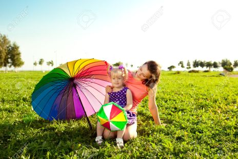 Cute little girl with mother colored balloons and rainbow umbrel